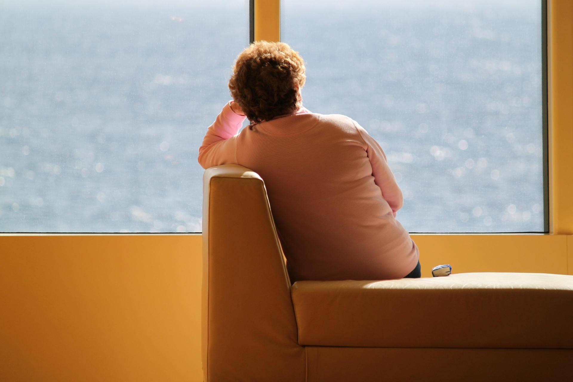 Kvinna sitter vid ett fönster och ser ut över öppet vatten