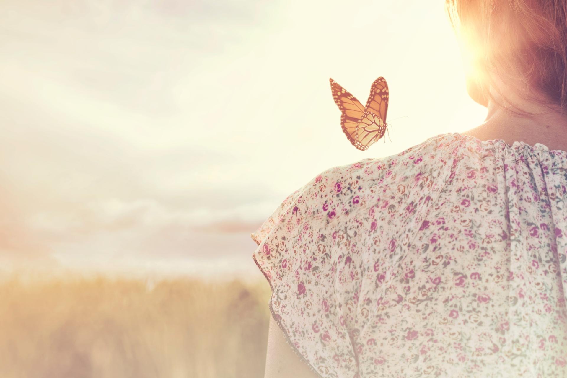 Fjäril landar på en kvinnas axel symboliserar personligt växande